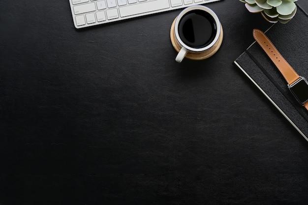 Scrivania in pelle scura con gadget per l'home office e spazio per copiare.