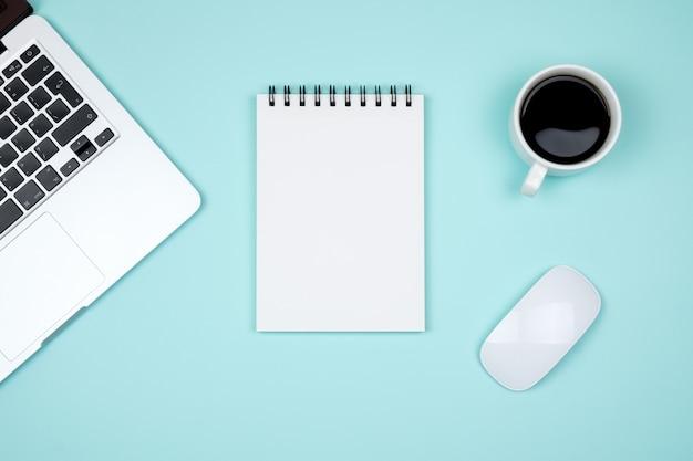 Scrivania minima con laptop e pagina di blocco note vuota