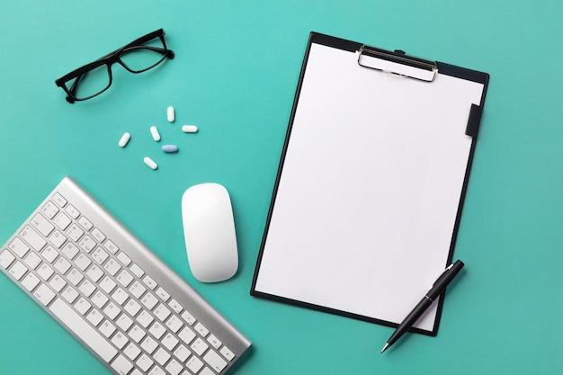 Scrivania per medici con tablet, penna, tastiera, siringa e fiale