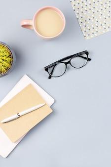 Scrivania per ufficio a casa piatta. area di lavoro femminile con taccuino, occhiali da vista, tazza da tè, diario, pianta. copia spazio