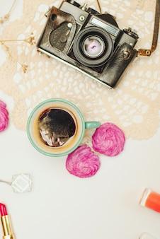 Scrivania piatta con caffè, zephyr, macchina fotografica vintage e cosmetici