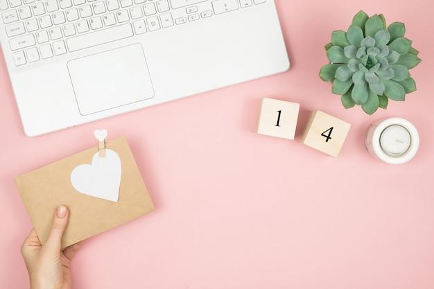 Scrivania piatta da ufficio. area di lavoro femminile con laptop, cosmetici, profumi, accessori sulla superficie rosa. busta lettera d'amore, cuore rosso san valentino