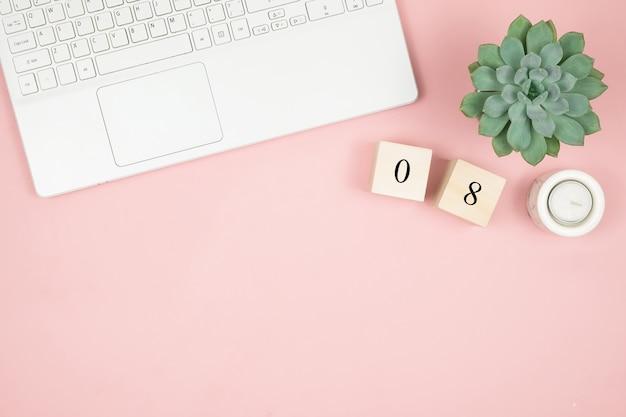 Scrivania piatta da ufficio. area di lavoro femminile con laptop e dati sulla superficie rosa. 8 marzo giornata mondiale della donna concetto