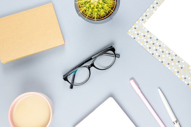 Scrivania piatta da ufficio. area di lavoro femminile con planner, occhiali, tazza da tè, diario, pianta. copia spazio