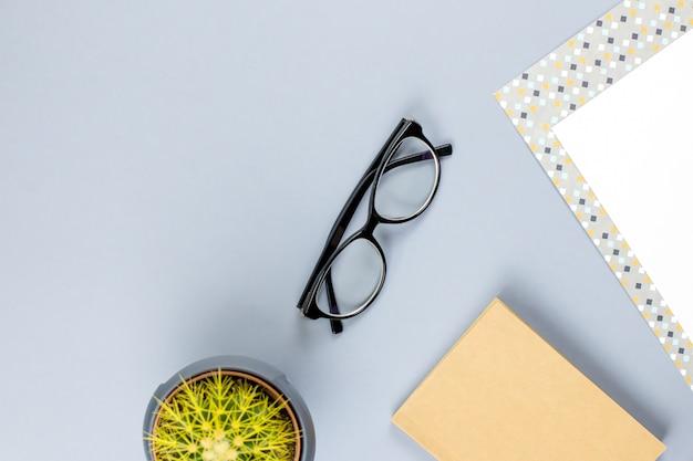 Scrivania piatta da ufficio. area di lavoro femminile con taccuino, occhiali, tazza da tè, diario, pianta. copia spazio