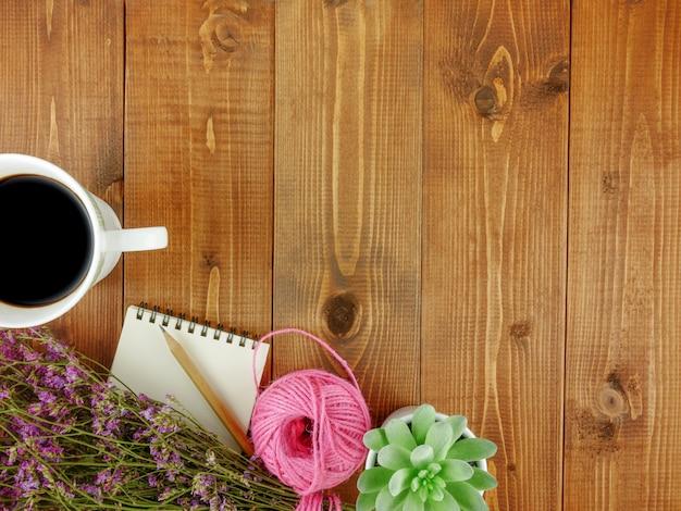 Scrivania piatta in legno marrone vista dall'alto, con elementi decorativi, una tazza di caffè, fiori e copia spazio