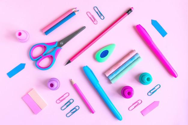 Scrivania rosa con varietà di materiale scolastico rosa e blu