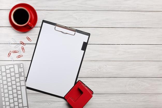Scrivania rossa del mouse della tastiera delle graffette dell'orologio della tazza di caffè della tazza di caffè della cartella del taccuino della cartella bianca dei tavoli