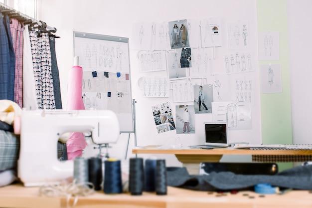 Scrivania stilista creativa o sul posto di lavoro con attrezzature per cucire, tessuti, modelli, ufficio ispiratore stilista moderno, atelier di sarta con vestiti appesi, showroom couturier