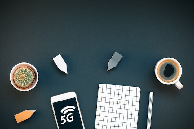 Scrivania sul posto di lavoro con smartphone 5g e tazza di caffè