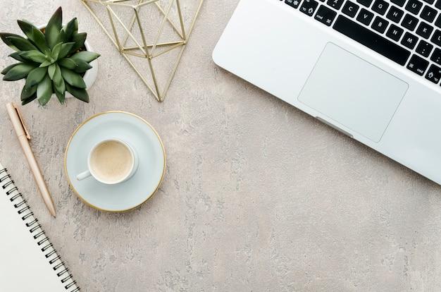 Scrivania vista dall'alto con caffè, pianta e laptop