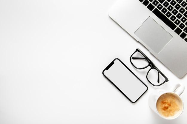 Scrivania vista dall'alto con laptop e telefono