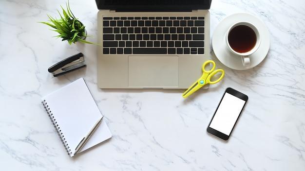Scrivania vista dall'alto tavolo in marmo laptop, caffè, smartphone e articoli per ufficio.