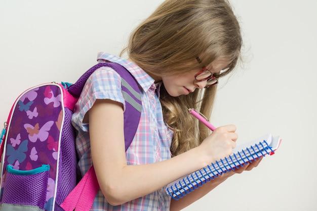 Scrive la giovane studentessa con gli occhiali e con lo zaino
