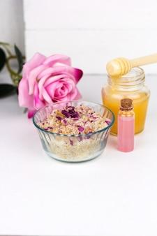 Scrub casalingo con sale marino, oli aromatici e petali di rosa e sfondo di miele jaerwhite