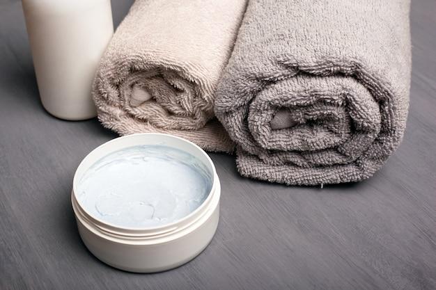 Scrub corpo e asciugamani arrotolati piegati colori pastello. prodotti per l'igiene per il bagno in primo piano.
