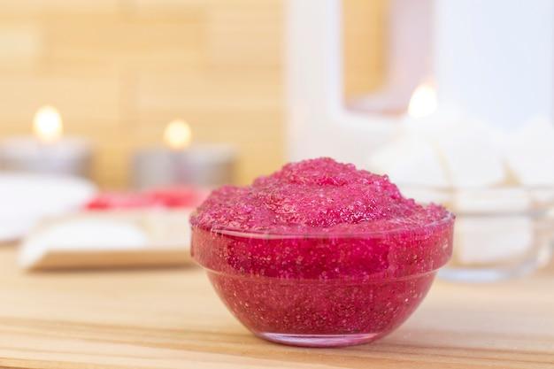 Scrub corpo rosa naturale a base di zucchero. il rosa sfrega in una tazza di vetro con candele e zucchero.