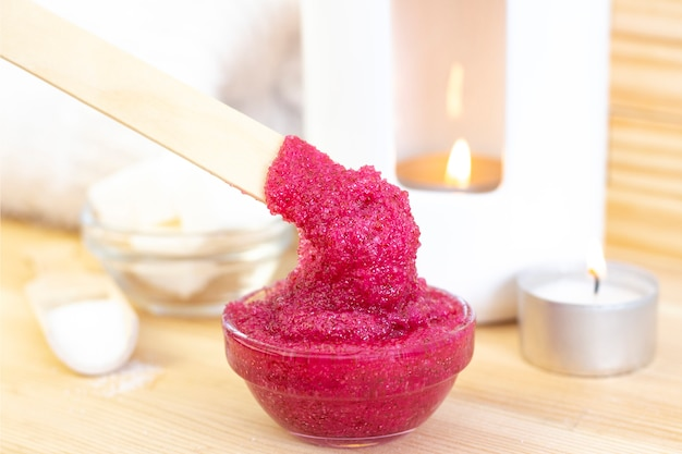 Scrub corpo rosa naturale a base di zucchero. il rosa sfrega in una tazza di vetro su uno sfondo di candele e zucchero.