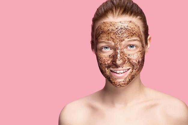 Scrub viso. ritratto di modello femminile sorridente sexy applying natural coffee mask, viso scrub sulla pelle del viso. primo piano di bella donna felice con la faccia coperta di prodotto di bellezza.