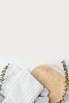 Scrubber per corpo luffa circolare; tovagliolo di cotone e pietre spa con ramoscelli isolati su sfondo bianco