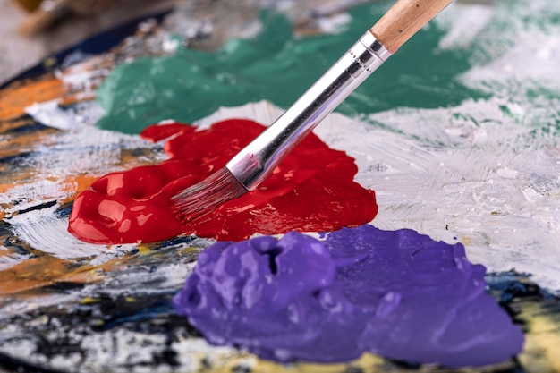Scuola d'arte. primo piano delle mani dell'artista che tengono tavolozza di legno, mescolando pittura acrilica con la spazzola.