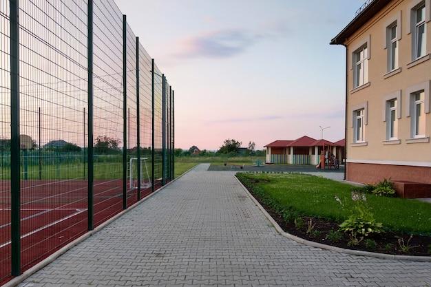 Scuola dell'iarda prescolare della costruzione con il campo da pallacanestro circondato con l'alto recinto protettivo.