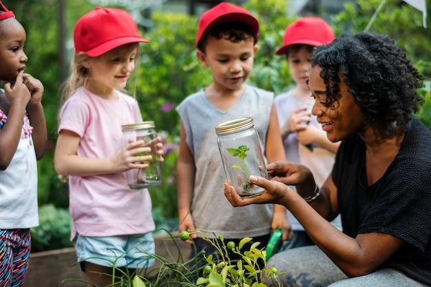 Scuola di insegnanti e bambini che imparano giardinaggio ecologico