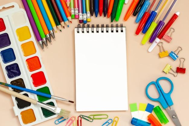 Scuola e articoli per ufficio con il blocco note vuoto sulla tavola.