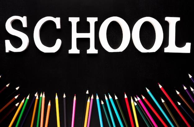 Scuola parola e matite colorate su sfondo nero
