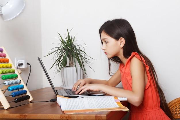 Scuola ragazza a casa sull'istruzione a distanza, homeschooling e fare i compiti al computer portatile durante la quarantena