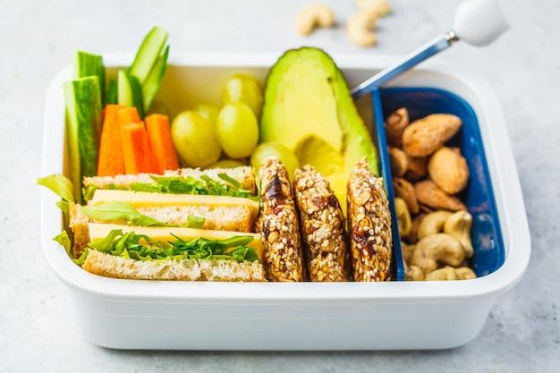 Scuola sana scatola di pranzo con sandwich, biscotti, frutta e avocado su sfondo bianco.