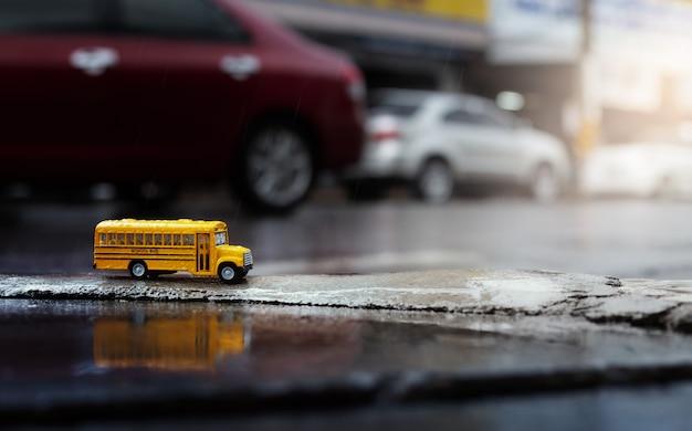 Scuolabus giallo (modello giocattolo) durante la caduta di forti piogge in città, vista ad angolo basso e composizione in profondità di campo.