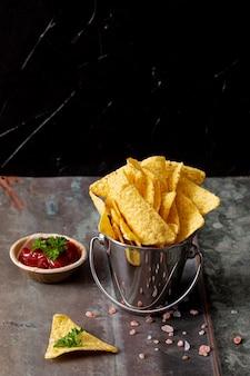 Secchio con nachos e salsa di pomodoro in una ciotola