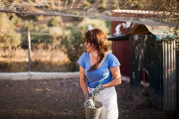 Secchio della tenuta della donna che sta nel campo