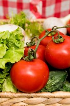 Secchio di close-up con pomodori e cetrioli