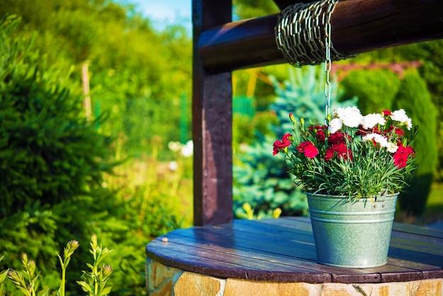 Secchio di fiori su un pozzo