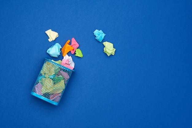 Secchio di metallo blu pieno di carta bianca sgualcita multicolore