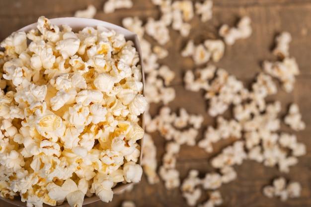 Secchio di popcorn per godersi il film su fondo di legno. vista dall'alto