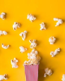 Secchio di popcorn piatto laici su sfondo giallo