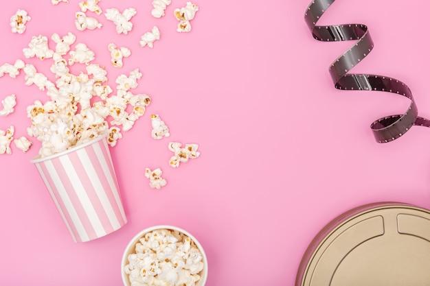 Secchio di popcorn, striscia di pellicola e pellicola può su sfondo rosa. sfondo di film o tv. vista dall'alto copia spazio