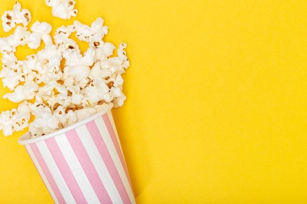 Secchio di popcorn su sfondo giallo. sfondo di film o tv. vista dall'alto copia spazio
