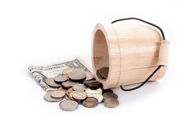 Secchio e denaro in legno, banconote in dollari usa, penny, nickel, dime, quarter