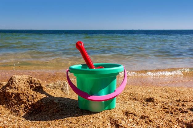 Secchio giocattolo di plastica per bambini con una paletta sulla riva sabbiosa della spiaggia del mare in una soleggiata giornata estiva