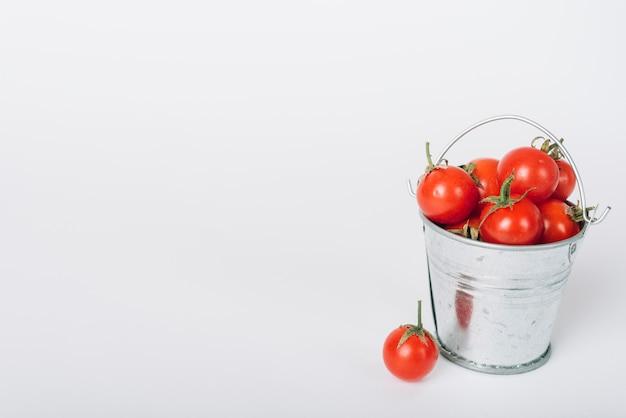 Secchio pieno di pomodori succosi rossi su sfondo bianco