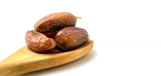 Secco dei frutti dolci della palma da datteri sul cucchiaio di legno su fondo bianco.