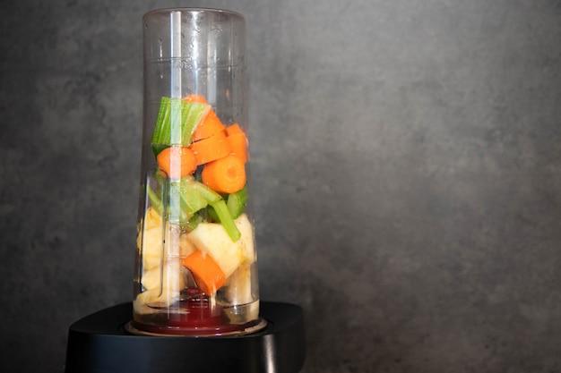 Sedano, mela e carota affettate in una tazza da frullatore per un frullato