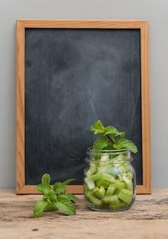 Sedano verde in barattolo e foglia di menta fresca sulla tavola di legno con la lavagna
