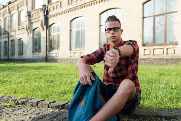 Sedendosi il ragazzo di scuola adolescente che esamina la macchina fotografica che disapprova