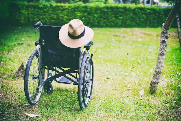 Sedia a rotelle con cappello nel parco.