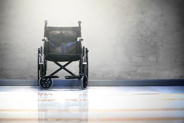 Sedia a rotelle in ospedale su sfondo di cemento grezzo con luce.